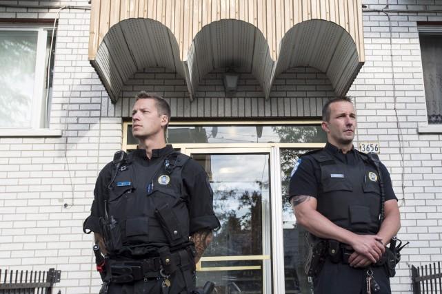 Des policiers montaient la garde devant un édifice... (La Presse canadienne, Paul Chiasson)