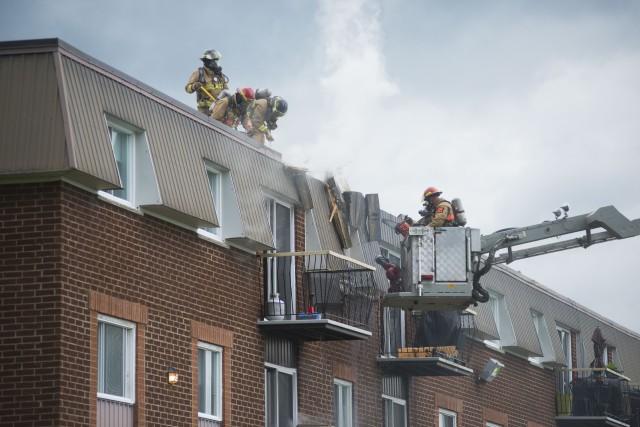 Ce sont des travaux avec une torche à la toiture du porche d'entrée arrière de... (Spectre Média, Julien Chamberland)