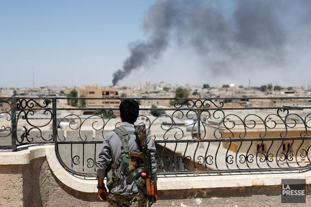 Un soldat kurde regarde la fumée s'élever dans... (REUTERS)