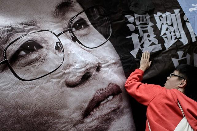 Un manifestant tient une banderole de soutien en... (PHOTO PHILIPPE LOPEZ, ARCHIVES AGENCE FRANCE-PRESSE)