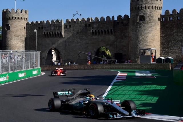 Sebastien Vettel (en arrière-plan) et Lewis Hamilton se... (Archives, AFP)