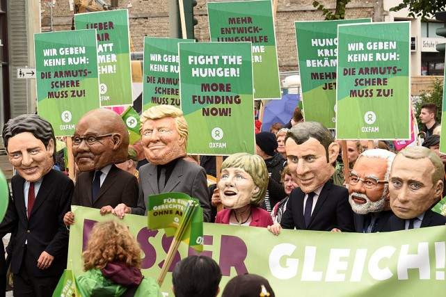 Des manifestants ont porté des masques représentant les... (PHOTO FABIAN BIMMER, REUTERS)