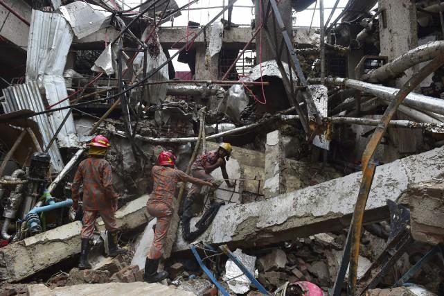 Les opérations de recherche dans l'usine près de... (AFP, Munir Uz Zaman)