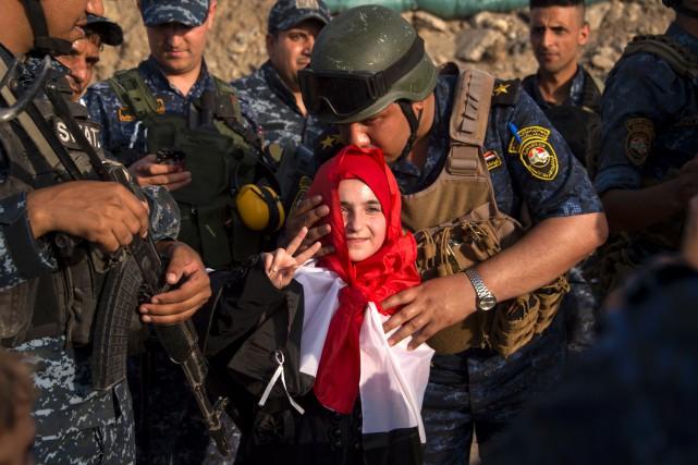 Un membre de la police fédérale irakienne embrasse... (PHOTO AFP)