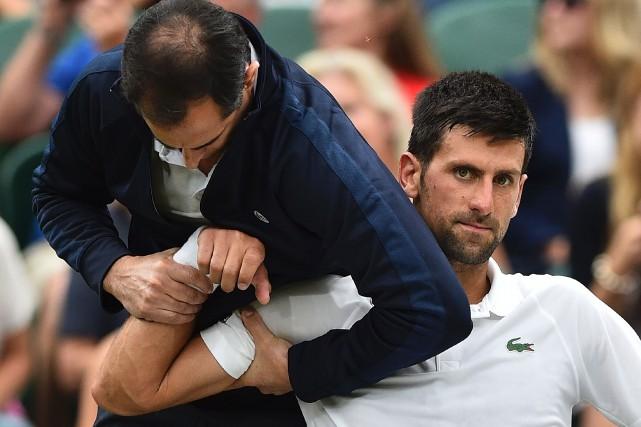 Blessé au coude droit, Novak Djokovic a été... (Photo Glyn Kirk, archives AFP)