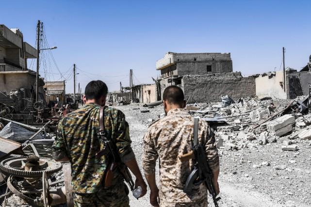 Des membres des Forces démocratiques syriennes marchent dans... (PHOTO BULENT KILIC, AFP)