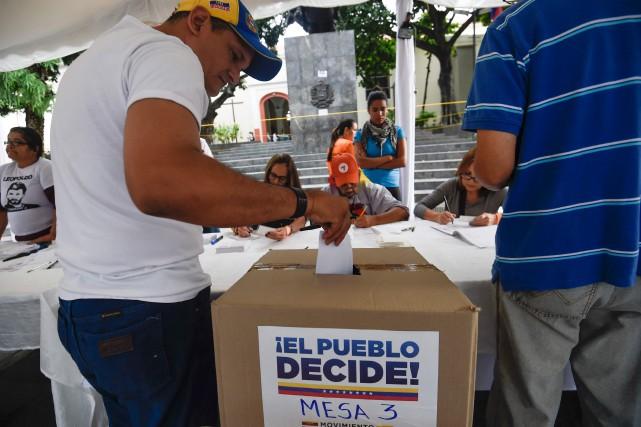 Un homme vote dimanche à Caracas lors d'un... (AFP, JUAN BARRETO)