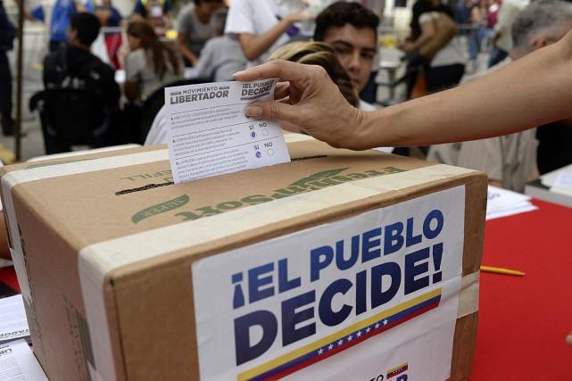 Une femme dépose son bulletin dans l'urne d'un... (PHOTO FEDERICO PARRA, AGENCE FRANCE-PRESSE)