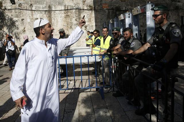 Un Palestinien argumente avec des policiers israéliens en... (PHOTO AHMAD GHARABLI, AGENCE FRANCE-PRESSE)