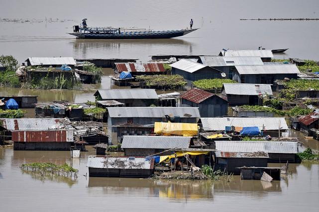 Un bateau circule près de maisons submergées dans... (PHOTO ANUWAR HAZARIKA, REUTERS)