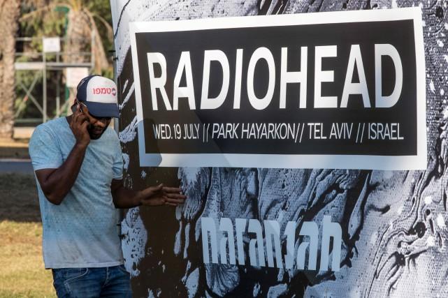 Un homme marche près de l'affiche du concert... (AFP)