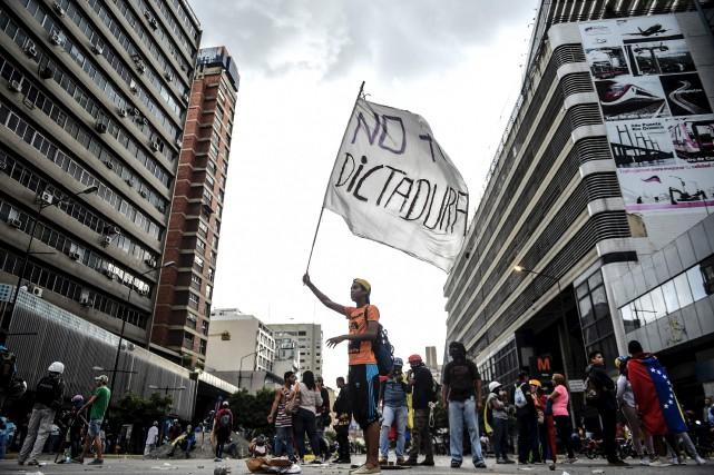 Un manifestant érige un drapeau sur lequel il... (AFP, JUAN BARRETO)