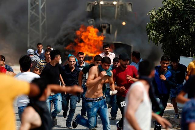 De jeunes Palestiniens se sauvent alors qu'un bulldozer... (PHOTO ABBAS MOMANI, AGENCE FRANCE-PRESSE)