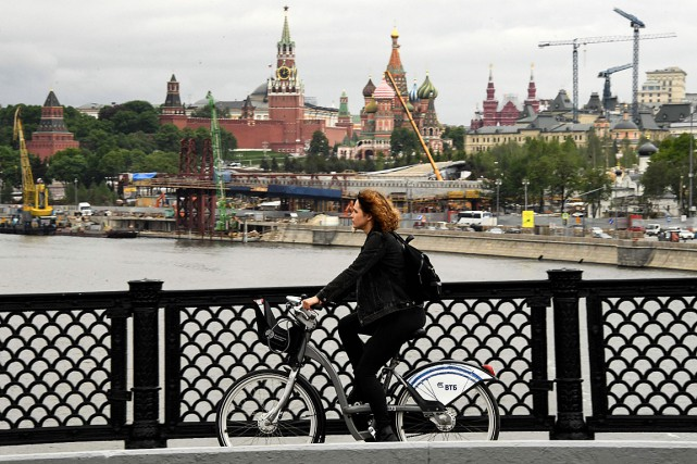 Une cycliste traverse un pont de Moscou, le... (PHOTO KIRILL KUDRYAVTSEV, AGENCE FRANCE-PRESSE)