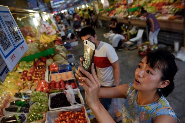 Cette femme numérise avec son téléphone portable un... (AFP, WANG ZHAO)