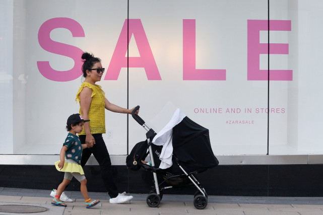 A woman walks with children past a sales... (REUTERS)