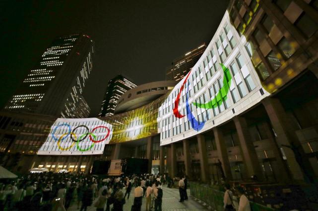 Des logos des Jeux olympiques sont projetés sur... (Associated Press)