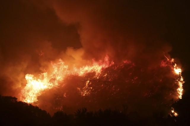 Peu avant minuit, les flammes étaient aux portes... (PHOTO Armando Franca, AP)