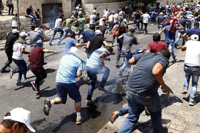 Des fidèles palestiniens courent après que la police... (PHOTO JACK GUEZ, AGENCE FRANCE-PRESSE)