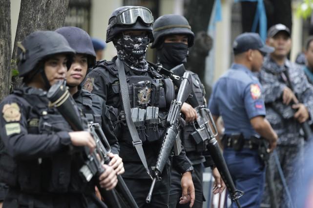 Des policiers montent la garde près du département... (PHOTO AP)