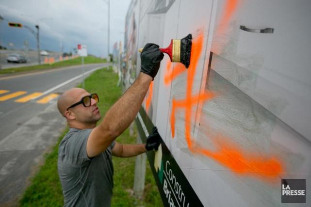 Corey Fleischer efface un graffiti haineux sur une... (PHOTO DAVID BOILY, LA PRESSE)