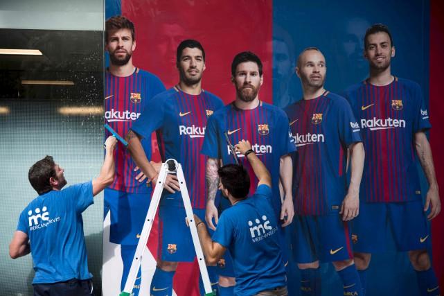 Deux hommes installent une nouvelle affiche des piliers... (AFP, Josep LAGO)