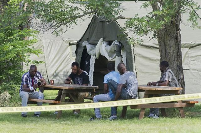 Des demandeurs d'asile haïtiens sont assis à des... (La Presse canadienne, Graham Hughes)