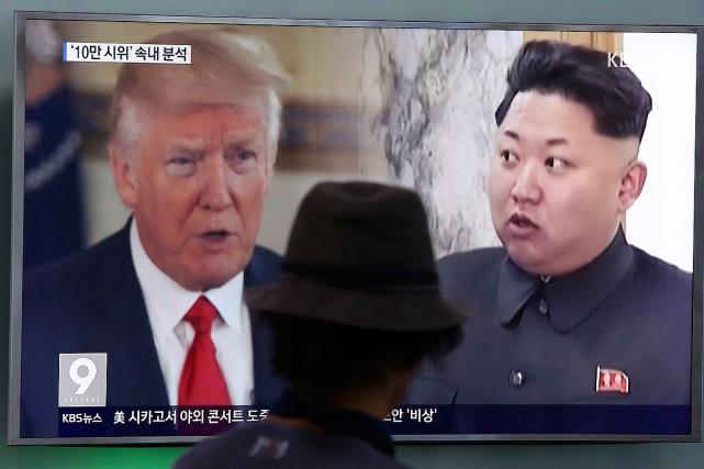 Un homme regarde un téléviseur affichant les visages... (Archives, Associated Press)