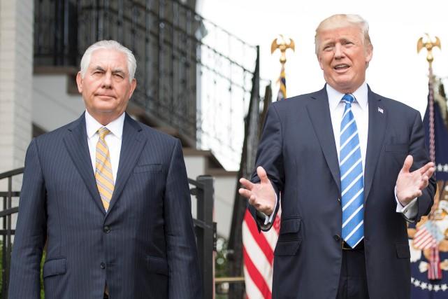 Flanqué du secrétaire d'État Rex Tillerson, Donald Trump... (AFP, Jim Watson)