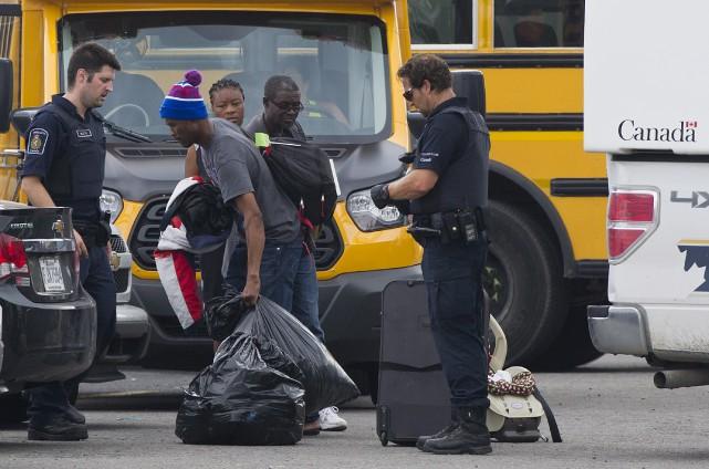 Des demandeurs d'asile récupèrent leur bagage à leur... (La Presse canadienne, Graham Hughes)