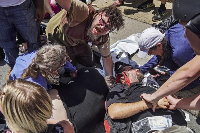Des gens appellent à l'aide après qu'une voiture... (PHOTO AP)
