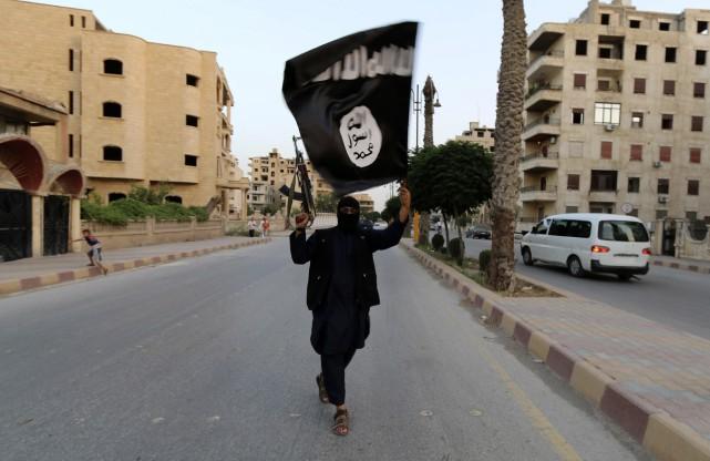 Un homme brandit le drapeau de l'EI à... (ARCHIVES REUTERS)