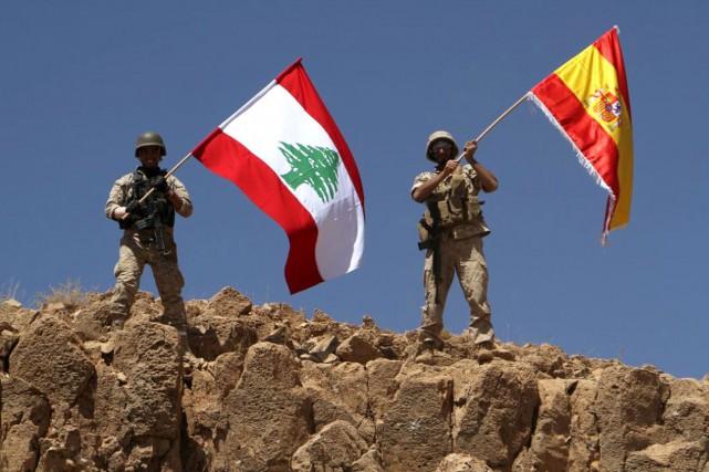 Des soldats libanais agitent les drapeaux du Liban... (AP)