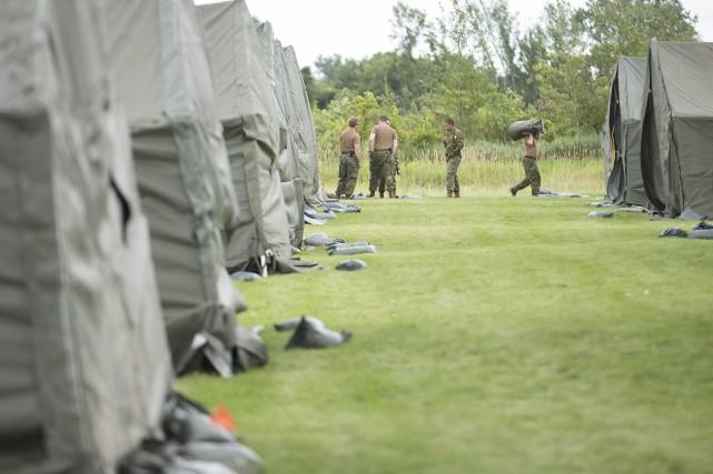 Des militaires préparent le campement pour les demandeurs... (Agence France-Presse)