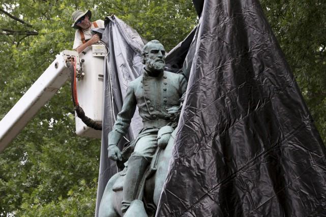 Un employé municipal recouvre l'imposante statuedu général confédéré... (AP, Steve Helber)