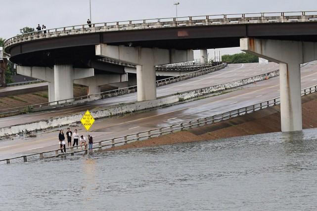 Des résidants observent lesinondations dubord d'une autoroute submergée,... (PHOTO AFP)