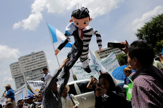 Des manifestants anti-gouvernement malmènent une piñata à l'effigie du... (PHOTO REUTERS)