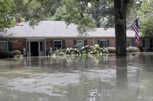 Un drapeau américain flotte devant une maison inondée... (AP)