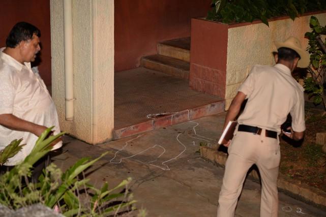 La police inspecte la scène de crime devant... (PHOTO AFP)