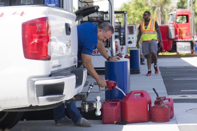 Un homme remplit des bidons d'essence dans une... (PHOTO AFP)