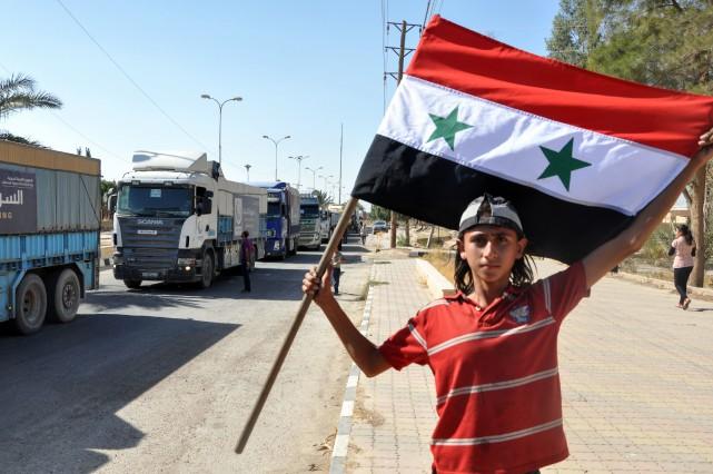 Un garçon brandit le drapeau syrien tandis que... (PHOTO AFP)