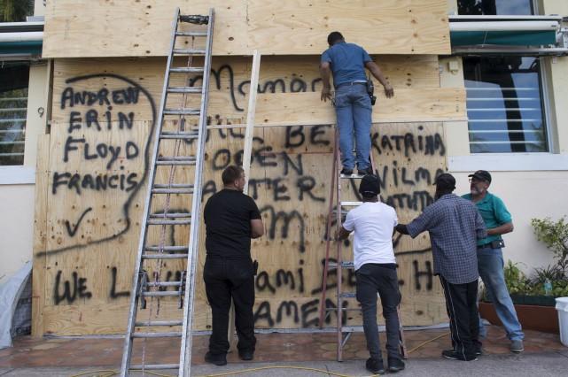 Des travailleurs placardent l'entrée de la boîte de... (AFP)