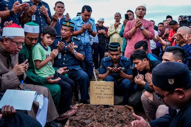Des gens sont réunis pour l'enterrement d'une des... (AFP, Sadiq Asyraf)