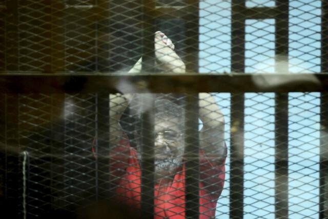 Mohamed Morsi derrière les barreaux pendant son procès,... (AFP, Mohamed al-Shahed)