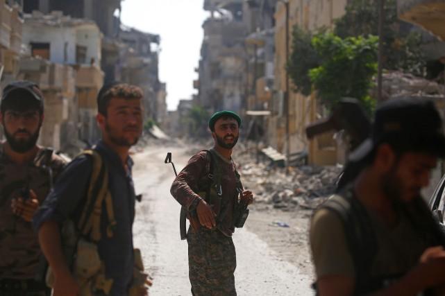 Des des Forces démocratiques syriennes marchent dans Raqqa... (PHOTO AFP)
