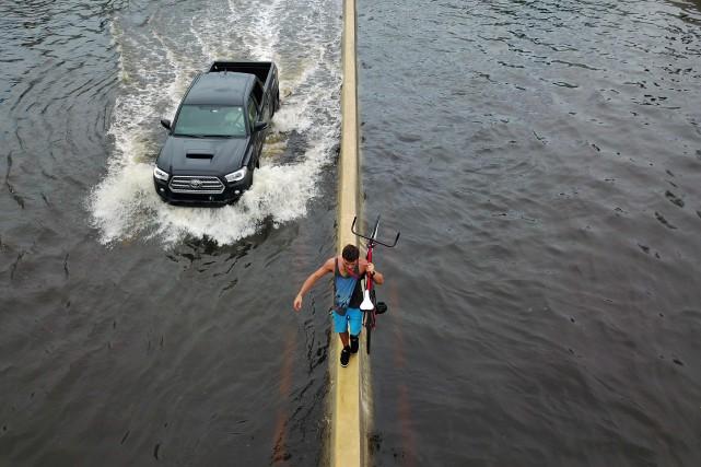 Un homme portant son vélo marche sur le... (PHOTO Ricardo ARDUENGO, AFP)