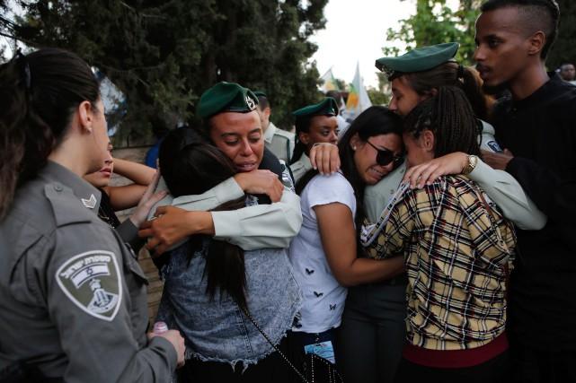 Des officiers et des proches s'enlacent pendant les... (PHOTO AFP)