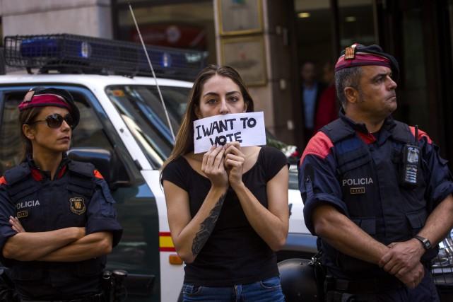 Entourée d'agents de la Garde civile, une femme... (PHOTO AP)
