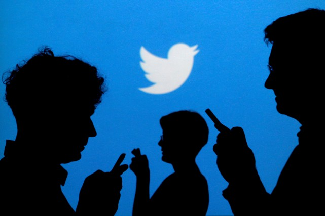 FILE PHOTO: People holding mobile phones are silhouetted... (ARCHIVES REUTERS)