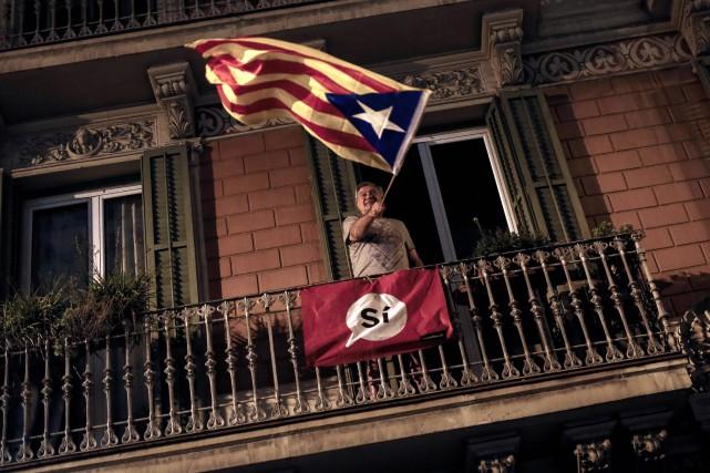 Un homme brandit un drapeau catalan depuis son... (PHOTO AFP)